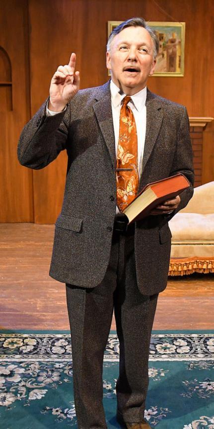 Jim Sherman standing, holding a book