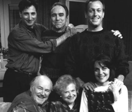 4 men and two women, all smiling, with arms around each other